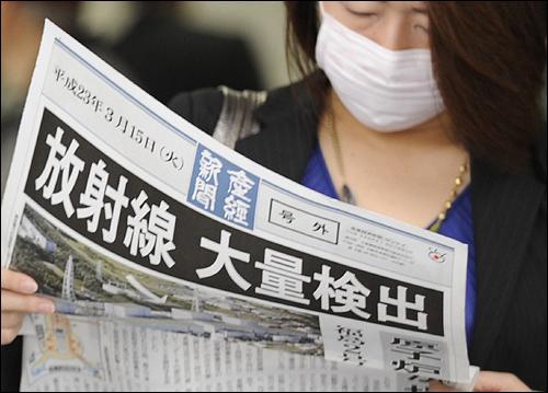15일 오사카 역 앞에서 한 시민이 후쿠시마 제1원자력 발전의 방사성 물질 유출을 전하는 호외를 보고 있다.