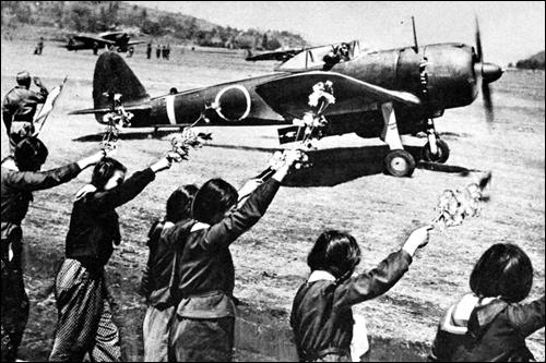 1945년 4월 12일 일본 치란 특공기지에서 출격하는 가미카제 특공대의 하야부사 전투기 조종사에게 벚꽃가지를 흔드는 일본 여고생들.