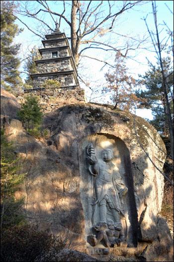 석불 암벽에 석불을 조각하고 위로는 탑이 서 있다.