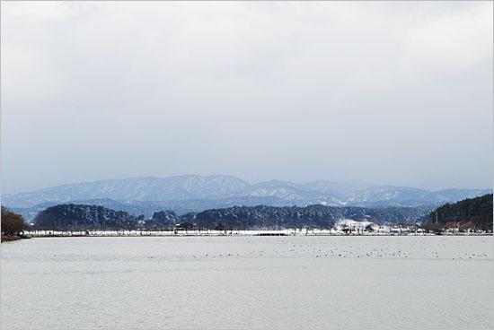 경포호 너머 멀리 눈덮인 설악산이 올려다 보인다.