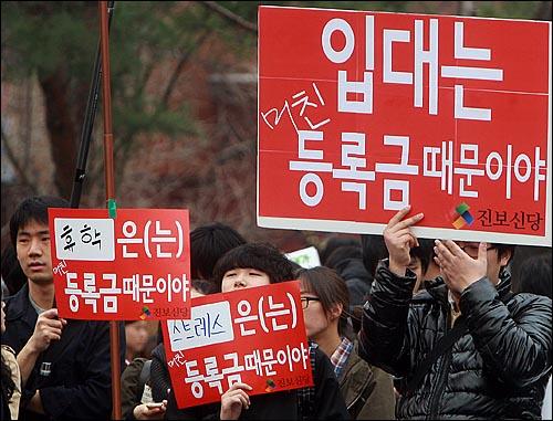 2일 오후 서울 종로구 대학로 마로니에 공원에서 등록금넷과 21세기 한국대학생연합 주최로 열린 '4.2 반값등록금 실현을 위한 시민·대학생 대회'에서 참가자들이 정부의 반값 등록금 공약 이행을 촉구하며 손피켓을 들어보이고 있다.