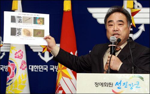 국립수산과학원 동해수산연구소 이 주 박사가 6일 오후 서울 용산 국방부 브리핑룸에서 천안함을 공격한 것으로 지목된 '1번' 글씨가 쓰인 어뢰추진체에 붙어 있는 붉은색 물체가 멍게가 아닌 것으로 확인됐다고 밝히고 있다. 국방부 조사본부는 어뢰 부착 물질에서 생물체 종류를 확인할 수 있는 어떤 유전자(DNA) 조각도 검출되지 않았으며 유전자 증폭실험을 통해서도 증폭된 DNA가 확인되지 않았다고 설명했다.
