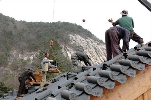 기와작업 홍두깨를 던지자 숙련된 모습으로 받아 기와작업을 진행시키고 있다.