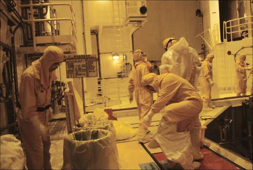 보이지 않는 공포 울진 원전의 격납용기 안에서 핵연료 교체 작업을 마친 직원들이 격납용기를 벗어나기 전에 비닐 방호복과 덧신을 벗고 있다.