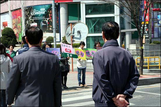 4.12 평화군축 캠페인 서대전네거리 횡단보도를 지나는 시민들이 캠페인 참가자들이 들고 있는 피켓을 유심히 살펴보고 있다.