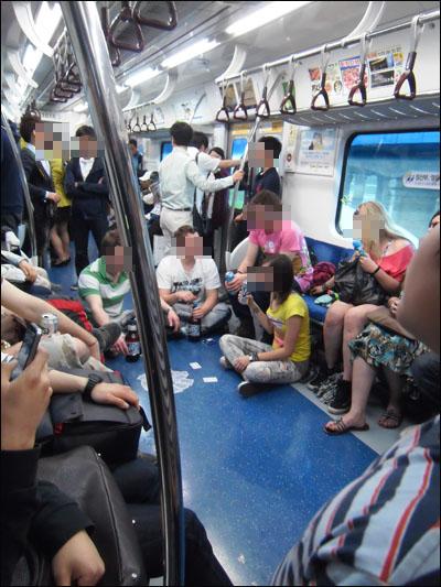 지하철 바닥에 앉아 술 마시며 포커게임을 하고 있는 외국인들.