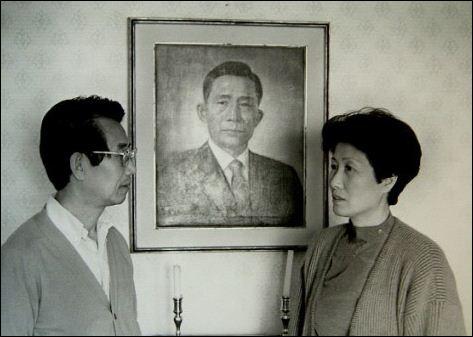 박정희 전 대통령의 맏딸인 박재옥씨와 남편 한병기씨가 박 전 대통령 사진 앞에 서 있다.