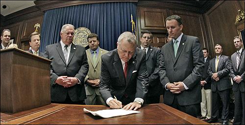 조지아 주의 네이튼 딜 주지사가 반이민법에 서명하고 있다. 오른쪽에 서 있는 사람이 법안 발의자인 공화당의 매트 램지 의원. 정치 신인이던 매트 램지 의원은 이번 법안으로 하루아침에 스타가 되었다.