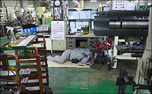 24일 오전 충남 아산시 소재 유성기업에서 한 조합원이 공장 바닥에 종이박스를 깔고 한뎃잠을 자고 있다.