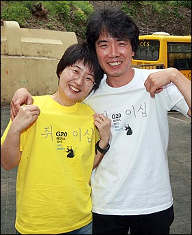G20 정상회의 홍보 포스터에 '쥐그림'을 그린 혐의로 벌금 200만원을 선고받은 대학강사 박정수씨(오른쪽)가 장애인 인권운동 벌금 충당용으로 제작된 쥐그림 티셔츠를 부인인 영화평론가 황진미씨와 함께 입고 포즈를 취하고 있다.