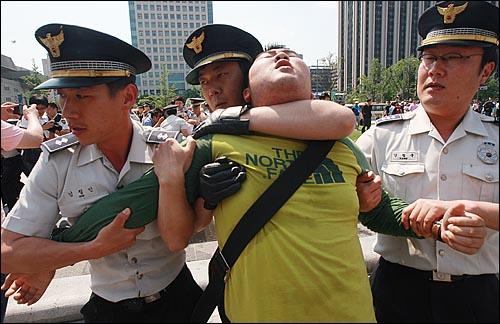 29일 오후 서울 광화문 광장에서 반값등록금과 청년실업 해결을 요구하며 시위를 벌이던 대학생들이 청와대로 행진을 시도하다가, 한 대학생이 경찰에게 목을 조인 채 강제연행되고 있다.