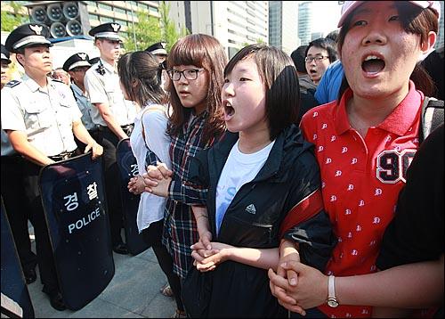 29일 오후 서울 광화문 광장에서 반값등록금과 청년실업 해결을 요구하며 시위를 벌이던 대학생들이 청와대로 행진을 시도하다가, 경찰들에게 강제연행되자 스크럼을 짜고 구호를 외치고 있다.