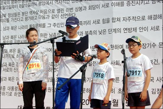 대전통일마라톤대회에 참가한 대구에서 온 김진현 씨 가족이 6.15공동선언 11주년을 기념하기 위해 6.15공동선언문을 낭독하고 있다.