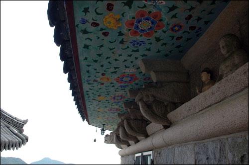 풍경 석재로 만든 대웅전 처마에 걸린 풍경. 부처님 모습도 보인다.