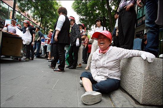 7일 오후 서울 인사동 문화의거리에서 영업을 시작하려는 노점상들을 구청 용역업체 직원들이 리어카를 뒤집으며 거칠게 저지하자, 한 여성 노점상이 주저앉아 울부짖고 있다.