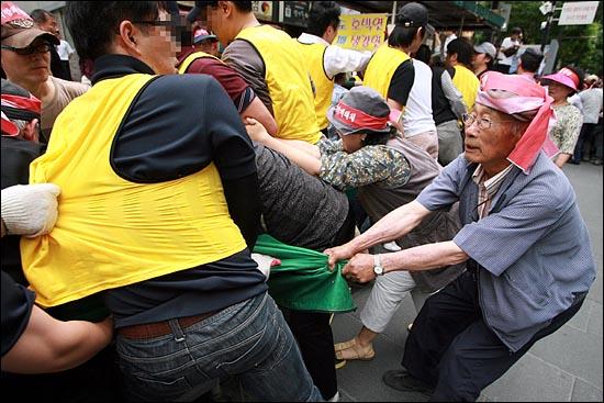 7일 오후 서울 인사동 문화의거리에서 영업을 시작하려는 노점상들을 구청 용역업체 직원들이 단속에 나서면서 아수라장이 벌어졌다. 구청 용역직원들에게 리어카를 뺏기지 않으려는 나이든 노점상들이 리어카를 붙잡고 있다.