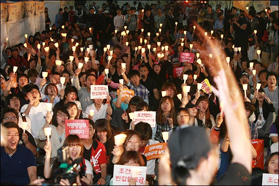 반값등록금 실현을 위한 12일차 대학생 촛불집회가 9일 오후 서울 청계광장에서 열린 가운데 참석자들이 서울종합예술원 조용훈 교수와 래퍼 김디지(본명 김원종) 교수의 공연에 촛불을 높이 들며 환호하고 있다.