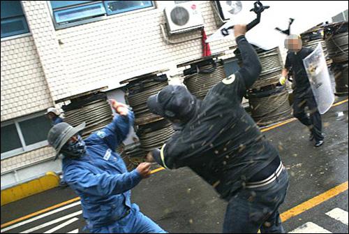 한진중공업 사측이 10일 오후 부산 영도조선소에 용역직원을 투입해서 노동자들과 충돌이 발생했다. 사진은 용역직원이 방패를 노동자한테 휘두르는 모습.