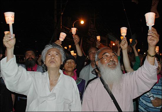 12일 오전 1시30분경 한진중공업 담을 넘어 들어온 백기완 통일문제연구소 소장과 문정현 신부가 집회에 참석해 촛불을 높이 들었다.