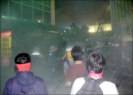 12일 새벽 담을 넘어 한진중공업 영도조선소 안으로 들어온 시민과 노동자들을 향해 정문 안 쪽에서 있던 용역경비원들이 소화기를 뿜어 아수라장이 되었다