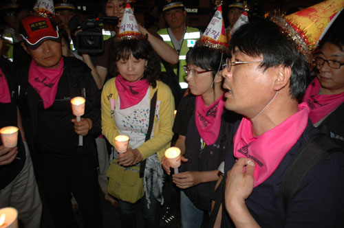 한진중공업 영도조선소 85호 크레인에서 정리해고 철회를 요구하며 158일째 고공농성을 벌이고 김진숙 지도위원을 지원하고 격려하기 위해 '희망버스'를 기획했던 송경동 시인이 기획팀인 '깔깔깔' 회원들과 촛불행진 도중에 이야기를 나누고 있다.