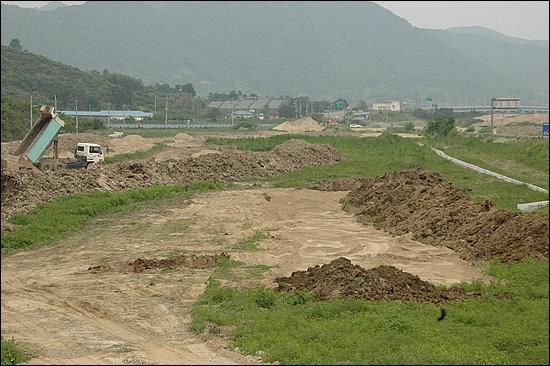 한국농어촌공사 창원지사가 발주한 '본포지구 농경지 리모델링사업' 현장으로, 낙동강에서 준설해온 모래와 흙이 쌓여 있다.