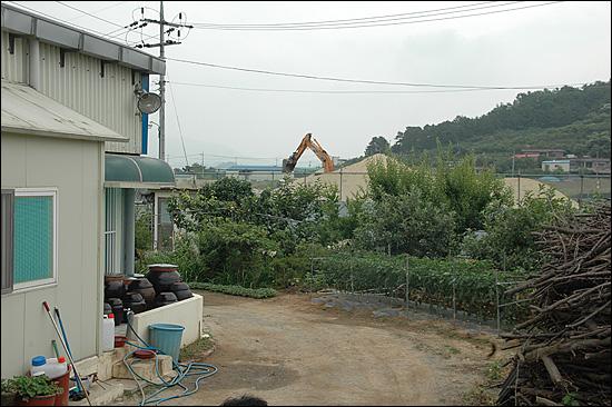 경남 창원시 동읍 본포리에 사는 박영복씨 집은 15년 전부터 지하수를 퍼올려 물을 사용해 왔는데, 최근 1주일 전부터 오염된 흙탕물이 계속 나오고 있다. 사진 왼쪽에 보이는 건물이 박씨의 집이며, 그 앞에 지하수를 퍼올려 담는 수도꼭지가 있고, 집 앞에는 농경지리모델링 사업을 벌이는 포크레인이 보인다.