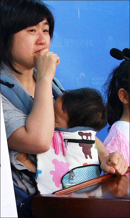 """한진중공업 해고자 가족인 도경정씨가 생후 11개월 된 아들(김성민)을 안고 나와 22일 국회 정론관에서 """"우리 애기아빠를 돌려달라"""" 눈물로 호소하고 있다."""
