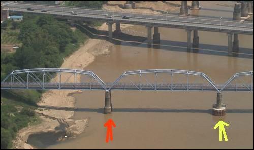 무너지기 직전의 다리 모습 노란 화살표는 교량보호공사를 하였습니다. 그러나 무너진 교량인 빨간 화살표의 교량은 전혀 보호공사가 안 되어 있음을 알 수 있습니다. 그런데 이 정부의 주장과는 달리, 무너진 교량은 분명히 강 물 속에 있고, 주변에 준설의 흔적이 보입니다.   특히 무너진 빨간색 교량 아랫부분 중 물밖에 노출된 부분이 준설로 인해 색의 차이 발생하고 있음을 알 수 있습니다. 물 밖의 교량이라 준설을 하지 않았다고, 보호공사를 할 필요가 없었다는 것은  거짓말입니다. 설사 이 교량을 직접 준설하지 않았다고 할지라도, 바로 곁 교량을 깊이 준설했다면, 홍수에 모래 강이 함께 세굴되어 피해가 발생한다는 것은 기초 상식입니다. 참으로 무지한 자들이 나라를 말아먹고 있습니다. 이명박 정부의 살리기란 이름의 진실이 바로 이것입니다.