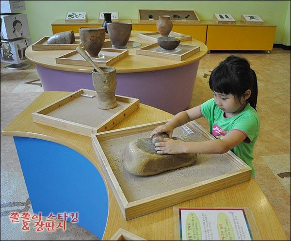선사 박물관에서 밀돌을 체험하고 있는 아이