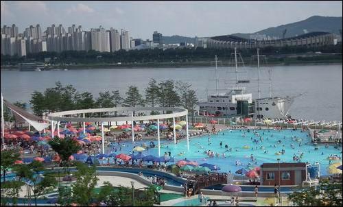한강 뚝섬 수영장. 뜨거운 햇살 아래 한강변 수영장을 많은 사람이 찾고 있습니다.