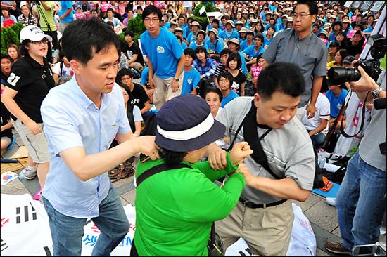 민주당 정동영 최고위원을 폭행한 여성이 행사관계자들에게 붙잡혀 끌려 나오고 있다.