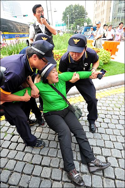민주당 정동영 최고위원을 폭행한 여성이 행사 관계자들에게 끌려나온후 거리에 넘어져 있자 주변에 있던 경찰기동대원들이 이 여성을 부축해 일으켜 세우고 있다.