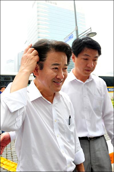 집회를 끝마친뒤 폭행과 관련된 기자의 질문에 정동영 최고위원이 쓴 웃음을 지으며 청계광장을 떠나고 있다.