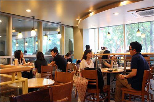 스타벅스 신촌점 매장 안에 사람들이 가득하다. 공부를 하는 학생, 담소를 나누는 연인 등 다양한 사람들이 커피전문점을 이용한다.
