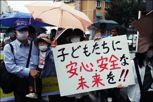 """7월31일 후쿠시마시에서 열린 탈핵을 요구하는 행진에서 참가자들이 """"아이들이 안심하고 안전할 수 있는 미래를 보장하라""""는 내용의 피켓을 들고 있다."""