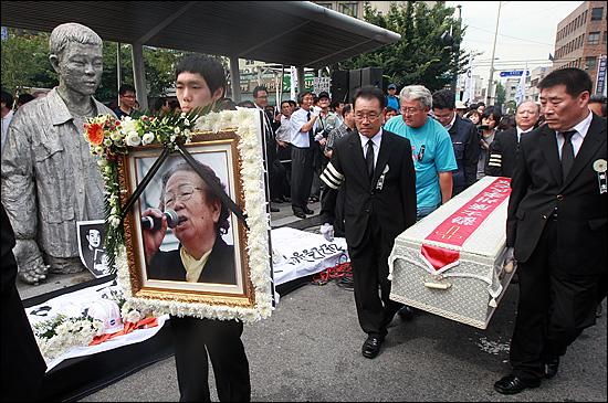 '노동자의 어머니 이소선 민주사회장'이 엄수된 7일 오후 서울 청계천 평화시장 앞 '전태일 다리'에서 열린 노제에서 고인의 영정사진과 운구가 아들의 동상 앞을 지나가고 있다.