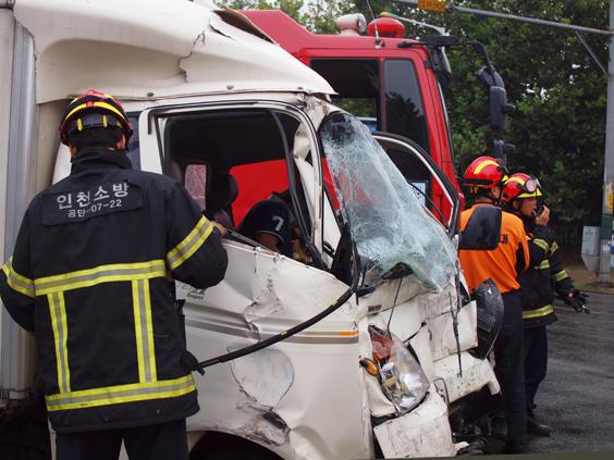 사고차량 소방대원이 사고차량의 상태를 살피고 있다 . 차량안에 사람이 보인다.