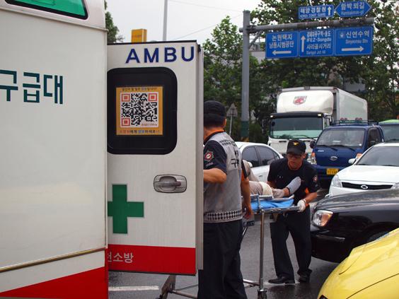 구급대 사고차량의 환자를 긴급 119 구급차에 실고 있다.