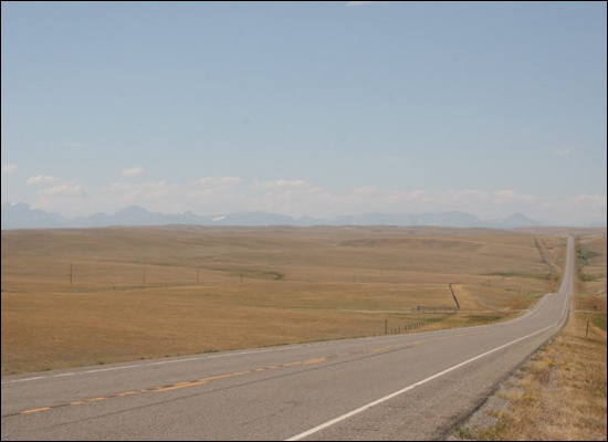 들과 산 US루트 89번 길 주변으로 들판이 펼쳐져 있다. 멀리 길 왼쪽으로 글래시어 국립공원을 구성하는 산들이 보인다.