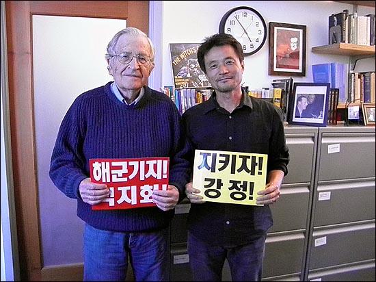 촘스키 교수가 고길천 화백과 함께 '해군기지 백지화' 카드를 들고 기념촬영을 하고 있다.