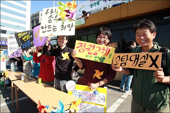 3일 서울시장 야권단일후보 선출을 위한 국민참여경선이 열린 장충체육관 앞에서 일부 참여자들이 '정권교체를 위한 선택'을 해달라는 피켓을 들고 투표참여를 호소하고 있다.
