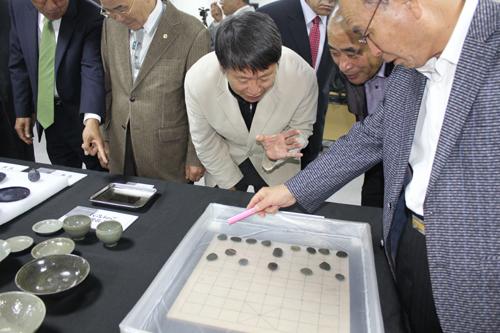 조약돌로 만든 장기돌 참석자들이 이번에 발굴된 장기돌을 보며 흥미로워하고 있다.