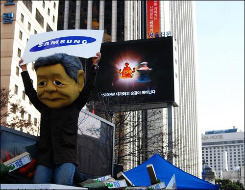 무릎 꿇은 삼성 기름유출사고의 책임을 묻는 피해지역주민과 시민사회단체의 항의집회가 서울서 열려 이건희 회장을 탈을 쓴 한 시민이 삼성로고가 새겨진 팻말을 들고 무릎을 끓은 모습