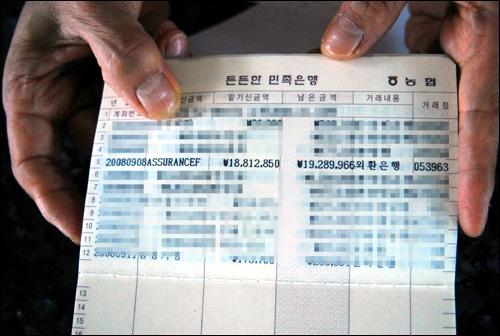 통장에 입급된 사정액 IOPC Fund로부터 사정된 피해액을 지급받은 한 주민이 통장을 보여주고 있다.