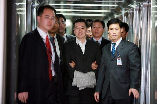 지난 2007년 11월 16일 '투자자문회사 BBK의 주가조작사건'의 핵심인물인 김경준 전 BBK 대표가 법무부 호송팀에 의해 수갑이 채워진 채 인천공항에 도착하며 밝은 표정을 짓고 있다.