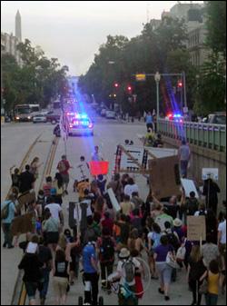 저 멀리 백악관이 보이는 거리를 따라 걷고 있는 시민들.