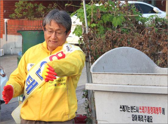 충남 서산시장 재선거에 출마한 국민참여당 임태성 후보의 선거운동 장면(쓰레기 청소).