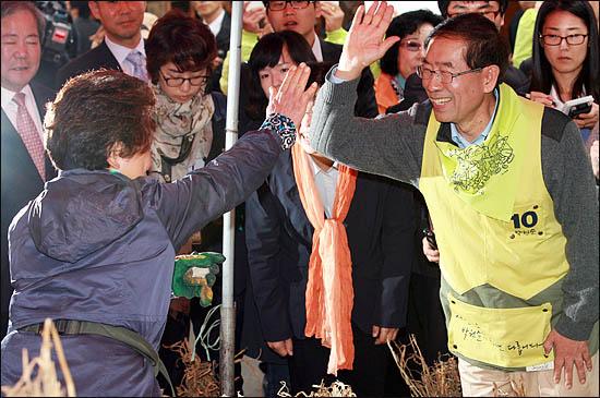 14일 오후 경동시장을 방문한 박원순 야권통합 서울시장 후보가 인사를 주고받은 한 상인과 하이파이브를 하고 있다.