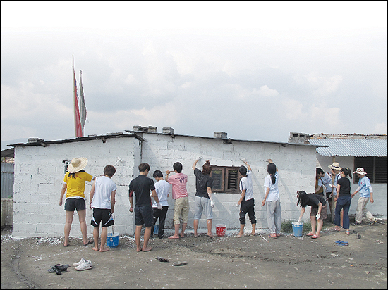 대안학교인 경남 태봉고등학교 학생들은 네팔 '짓다만 학교 짓기'를 위해 '네팔 기부 펀드' 모금 운동을 벌이고 있다. 사진은 지난 5월 네팔을 방문했던 태봉고 학생들이 학교 건물 벽면에 페인트를 칠하는 모습.